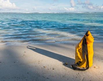 Segelbeutel steht am Meer im Sand