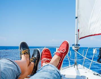 Segler liegen mit ihren Bootsschuhen an Deck einer Yacht