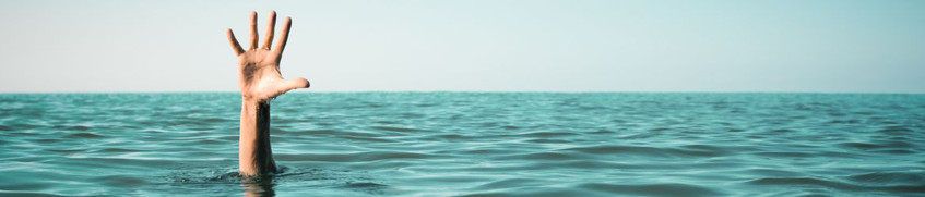 Seekrankheit vorbeugen: Hand ragt aus der See