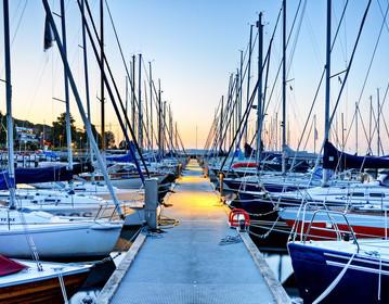 Charter-Beschlagnahmeversicherung: Segelboote im Hafen bei Sonnenuntergang