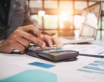 Mann rechnet mit Taschenrechner Kosten der Risikolebensversicherung aus