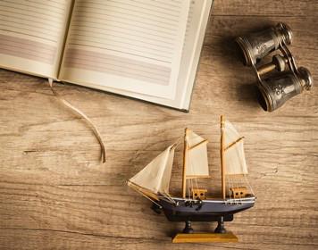 Leeres Logbuch und Modellboot auf Holztisch