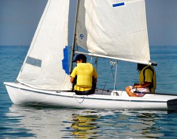 Zwei Kinder auf Boot lernen das Segeln