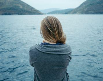 Mittel gegen Seekrankheit: Frau starrt auf Wasser