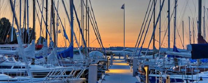 Reiserücktrittsversicherung: Segelboote im Hafen bei Sonnenuntergang