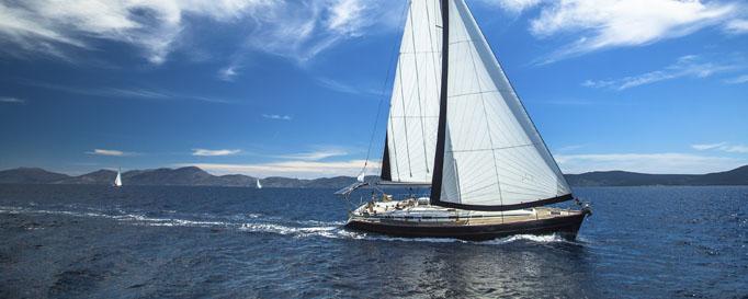 Segeln Baltikum: Segelboot vor bergiger Küstenlinie
