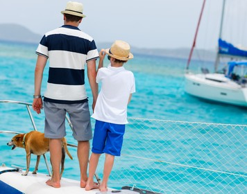 Mann mit Kind und Hund an Deck eines Segelboots