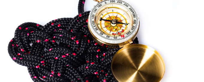 Segeln lernen: Kompass neben schwarzem Seegarn