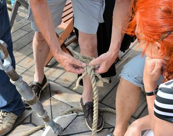 Segeln lernen - Gruppe übt Knoten