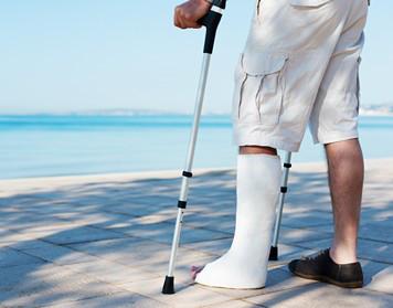 Mann mit Gips profitiert von Reiserücktrittsversicherung