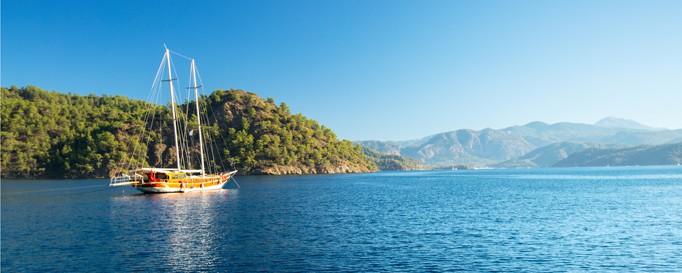 SKS: Segelboot auf See vor bewaldeter Küste