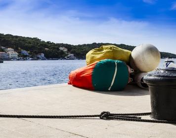 Bunte Segeltaschen liegen auf einem Steg